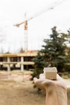 Main tenant la petite maison modèle devant le chantier de construction, concept immobilier