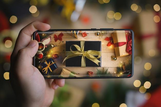 Main tenant une photo du cadeau de noël en or noir avec un smartphone à affichage infini