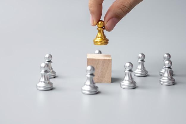 Main tenant des pièces de pion d'échecs dorés ou un homme d'affaires leader. concept de victoire, de leadership, de réussite commerciale, d'équipe, de recrutement et de travail d'équipe