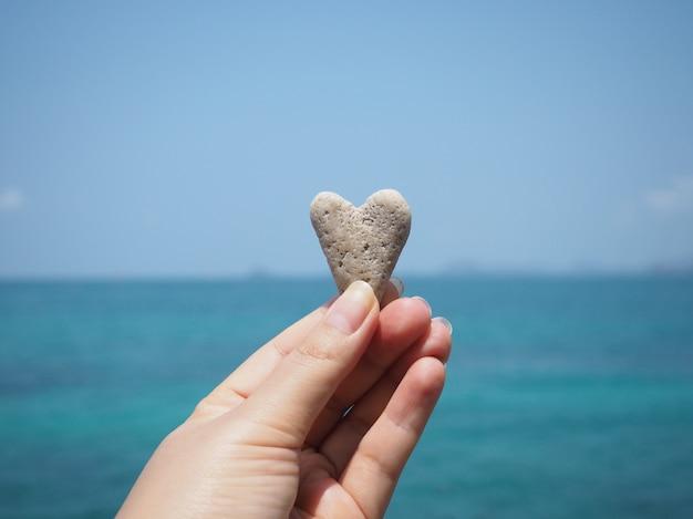 Main tenant la pierre en forme de coeur sur fond de plage l'été