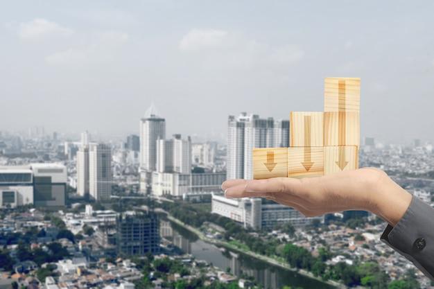 Main tenant la pile de jouet de bloc en bois avec flèche vers le bas avec fond de paysage urbain