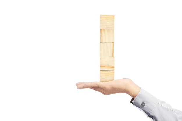 Main tenant la pile de jouet de bloc en bois isolé sur fond blanc