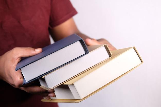 Main tenant la pile de livres sur un mur blanc
