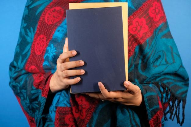 Main tenant la pile de livres sur le mur de couleur
