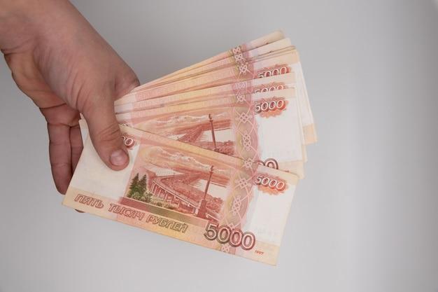 Main tenant la pile de roubles russes.