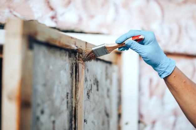 Main tenant un pinceau en appliquant de la peinture au vernis sur une porte en bois