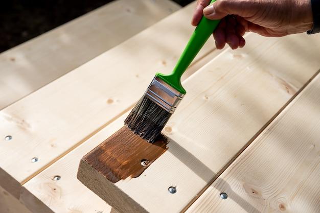 Main tenant un pinceau appliquant de la peinture vernis sur une surface en bois