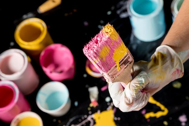 Main tenant le pinceau avec de la peinture colorée