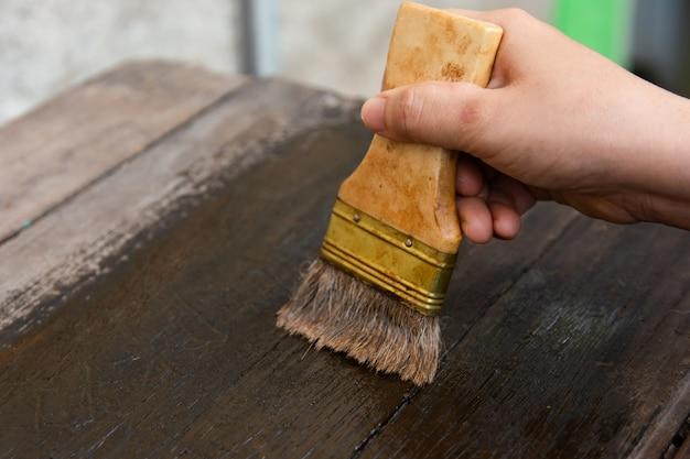 Main tenant un pinceau peinture des planches en bois avec du bois
