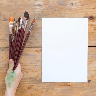 Main tenant des pinceaux en bois près de papier blanc