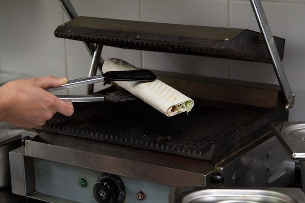 Main tenant des pinces de cuisine avec falafel