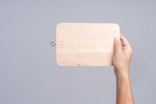 Main tenant une planche à découper en bois pour la cuisine
