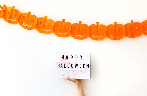 Main tenant une planche avec écriture près de la décoration de l'halloween