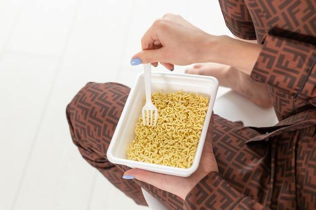 Main tenant la plaque avec des nouilles chinoises instantanées, insuffisance rénale à haut risque de régime de sodium. mauvais pour la santé