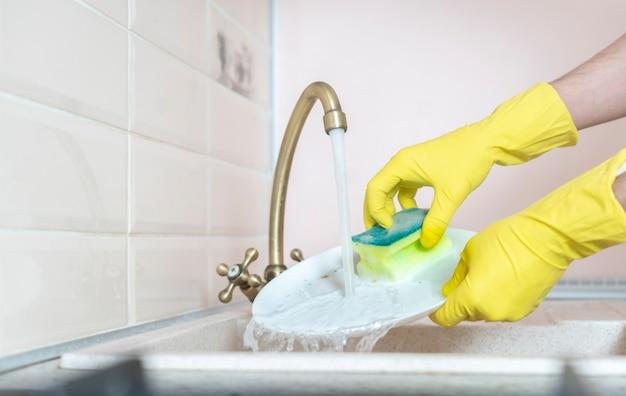 Une main tenant un plat sale et le laver dans l'évier de la cuisine en versant de l'eau