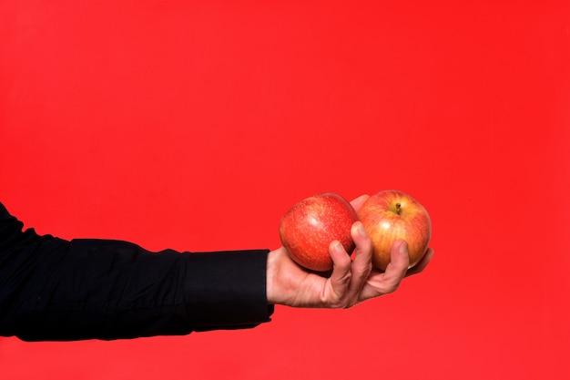 Main tenant une pomme deux sur fond rouge