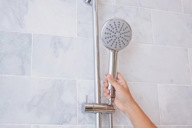 Main tenant la pomme de douche pendant la douche