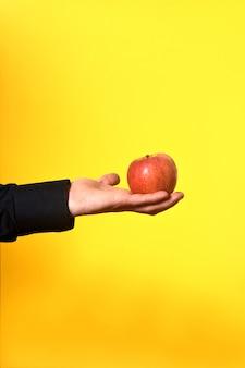Main tenant une pomme sur fond jaune