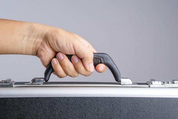 Main tenant un porte-documents en métal avec verrou de sécurité