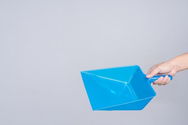 Main tenant un porte-poussière en plastique bleu portable