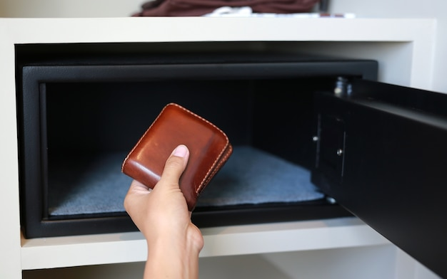 Main tenant un portefeuille marron dans un coffre-fort.