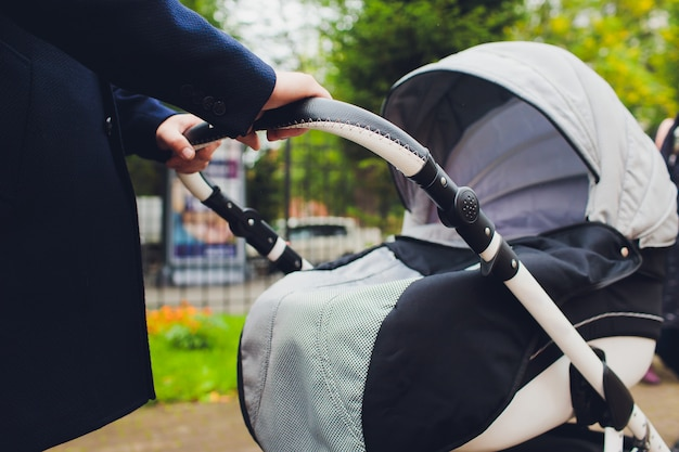 Main tenant une poussette de bébé.