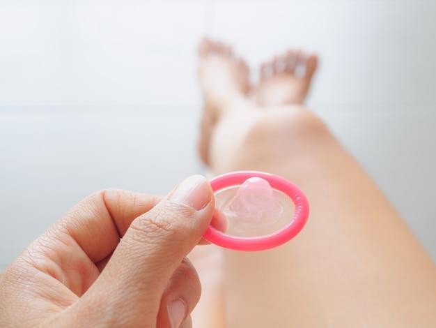Main tenant le préservatif et les jambes sexy