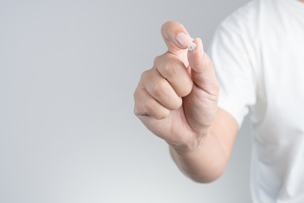 Main tenant une punaise pour papier ou carton