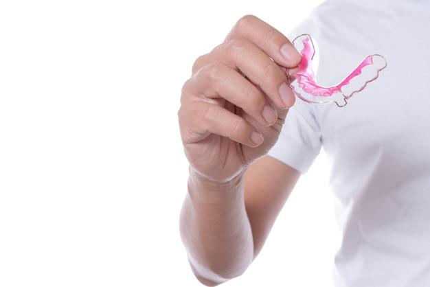 Main tenant une retenue dentaire en acrylique ou des accolades pour les dents avec une prothèse dentaire