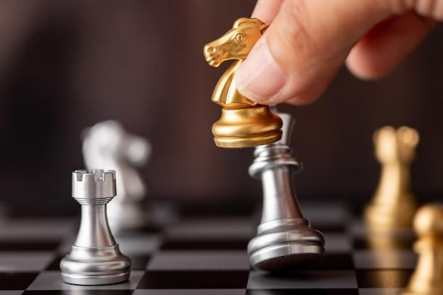 Main tenant le roi d'argent d'attaque de cheval d'or dans le jeu