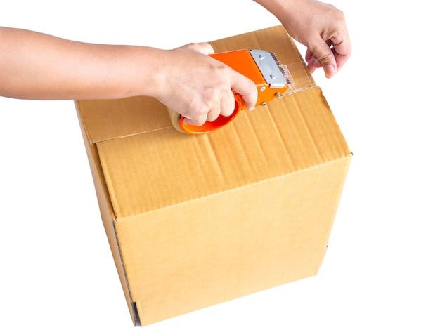 Main tenant un rouleau de ruban d'emballage en plastique transparent et une boîte brune isolée sur fond blanc.