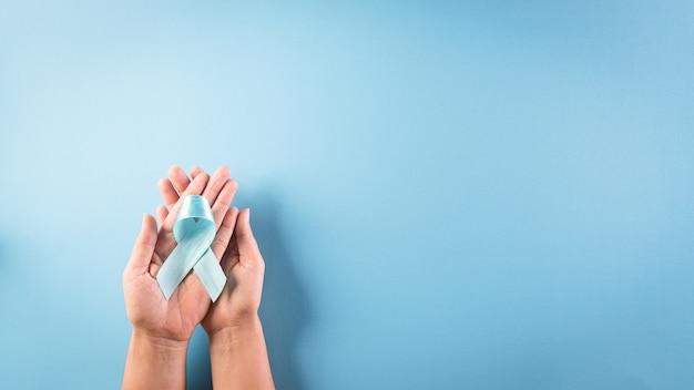 Main tenant le ruban bleu, couleur de l'arc symbolique sensibilisant à la journée du diabète
