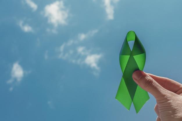 Main tenant un ruban vert sur ciel bleu
