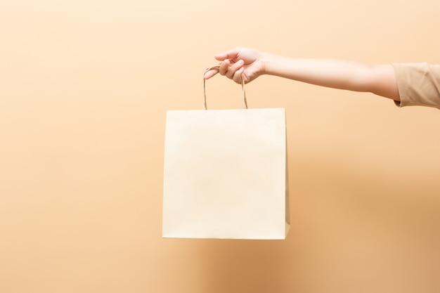 Main tenant un sac en papier isolé sur fond