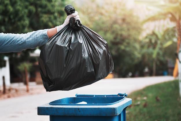 Main tenant un sac poubelle noir mettant à la poubelle