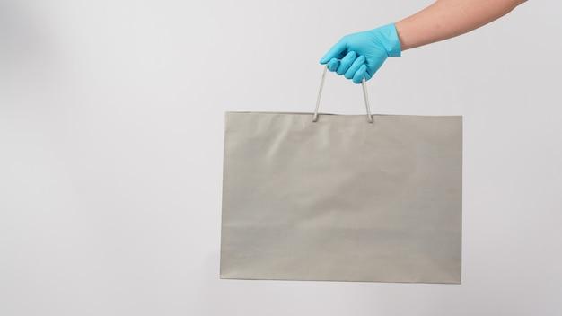 Main tenant un sac à provisions gris et porter un gant médical bleu isolé sur fond blanc.