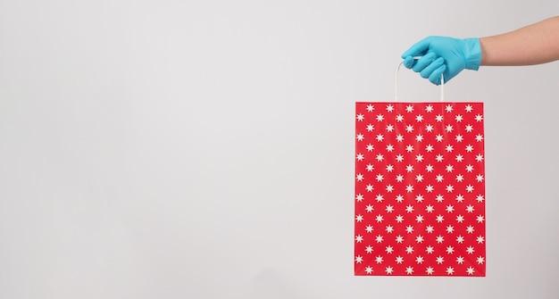 Main tenant un sac à provisions rouge et porter un gant médical bleu isolé sur fond blanc.