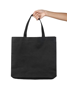 Main tenant un sac en toile de tissu noir vierge isolé