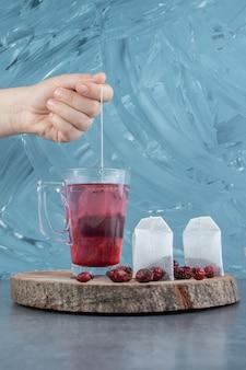 Main tenant un sachet de thé sur bleu clair.