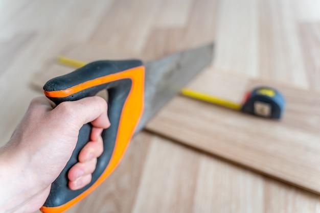 Main tenant une scie pour la préparation du panneau stratifié mesuré avec un ruban à mesurer jaune.