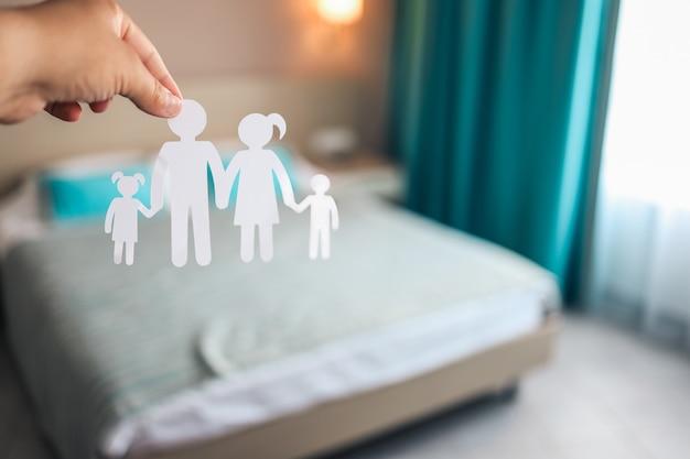 Main tenant la silhouette de la famille du papier sur l'arrière-plan de la chambre floue de l'hôtel.