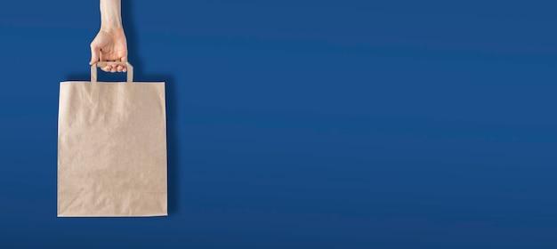 Une main tenant un simple sac en papier vierge contre le mur, concept zéro déchet et recyclage