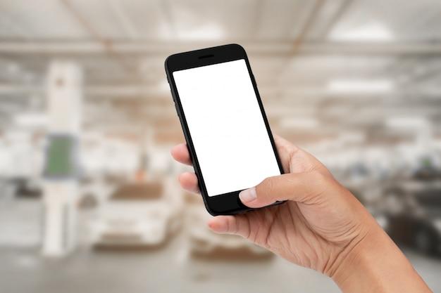 Main tenant le smartphone avec abstrait floue du fond de la voiture de stationnement.