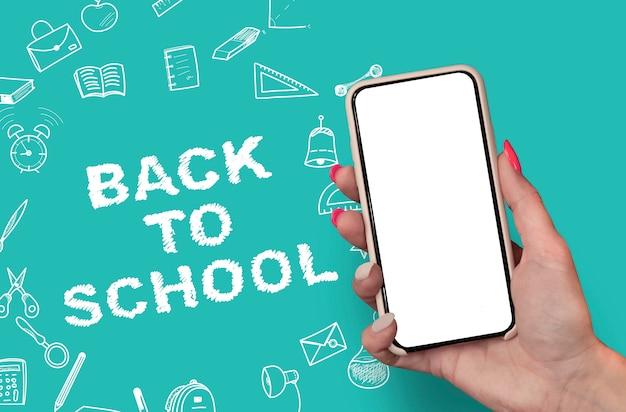 Main tenant un smartphone blanc sur fond de griffonnages d'école de papeterie