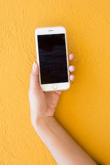 Main tenant un smartphone blanc sur fond de mur jaune