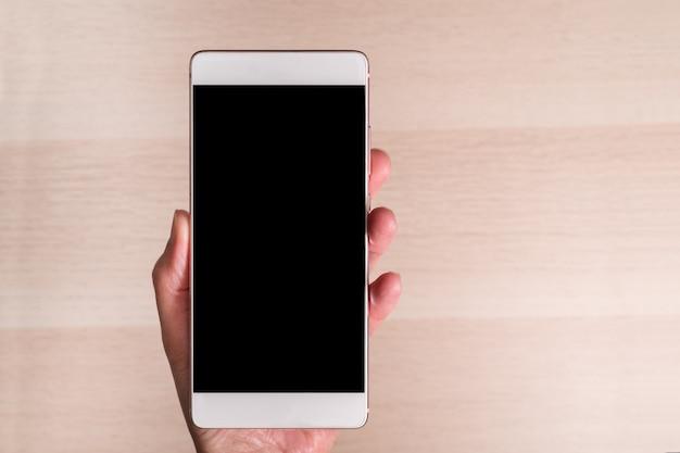 Main tenant le smartphone avec écran blanc isolé sur fond en bois