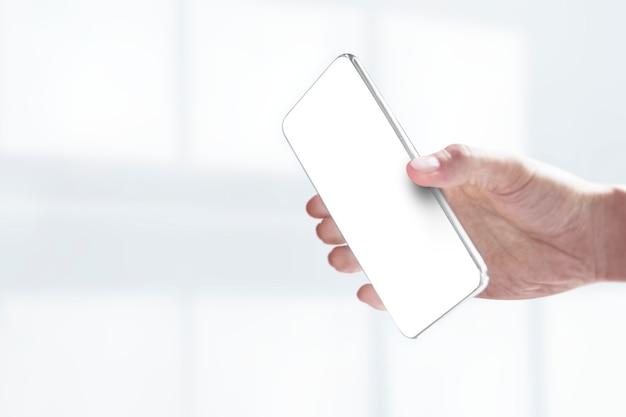 Main tenant un smartphone avec écran blanc