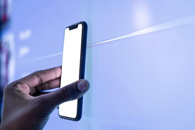 Main tenant le smartphone avec écran blanc