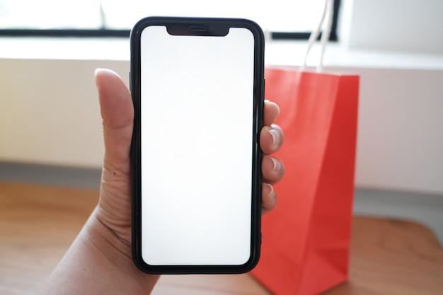 Main tenant le smartphone avec un écran vide pour l'espace de la copie.