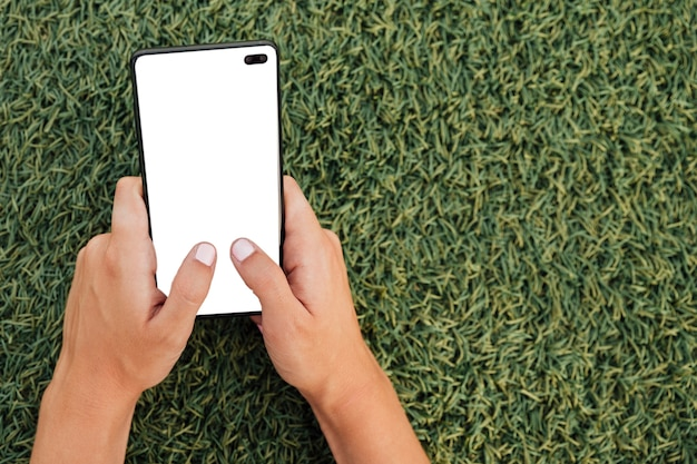 Main tenant un smartphone moderne avec maquette